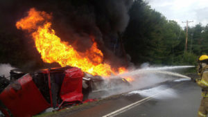 A firefighter uses water to cool a gasoline truck that overturned on Route 27 near Diamond, PA, in 2014